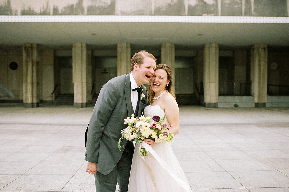 Newlyweds, Ashley and Ed, laughing with joy in the heart of New Orleans.