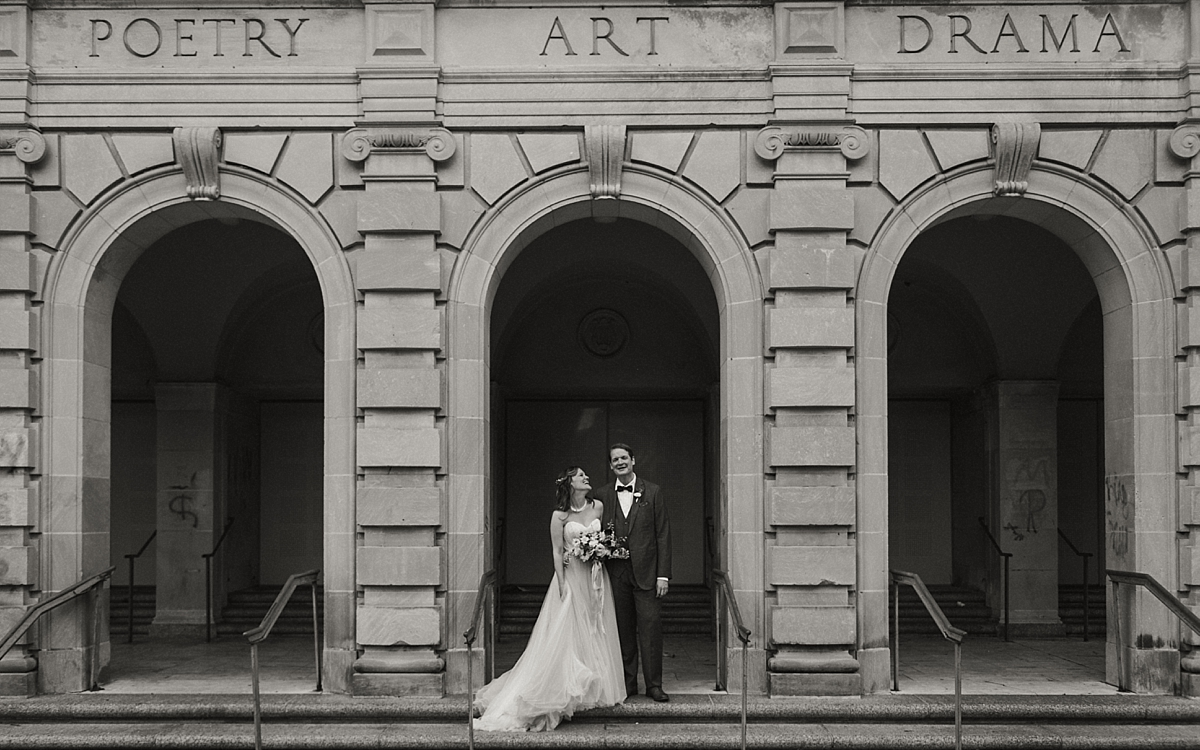 Ashley and Ed smiling for their iconic New Orleans portrait under the arches in Louis Armstrong Park.