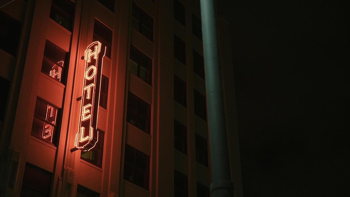 The neon Ace Hotel New Orleans sign lit up at night from street view.