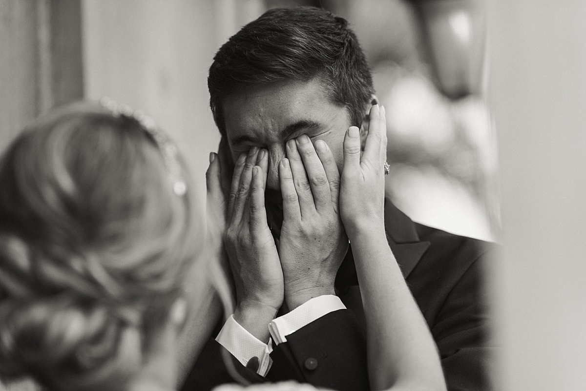 Anna reaches for Oli's face as he covers his eyes with his hands after seeing her in her dress for the first time.
