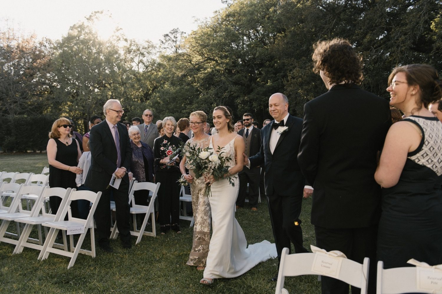 Caroline walks down the isle on the lawn of the Paul and Lulu Hilliard Art Museum.