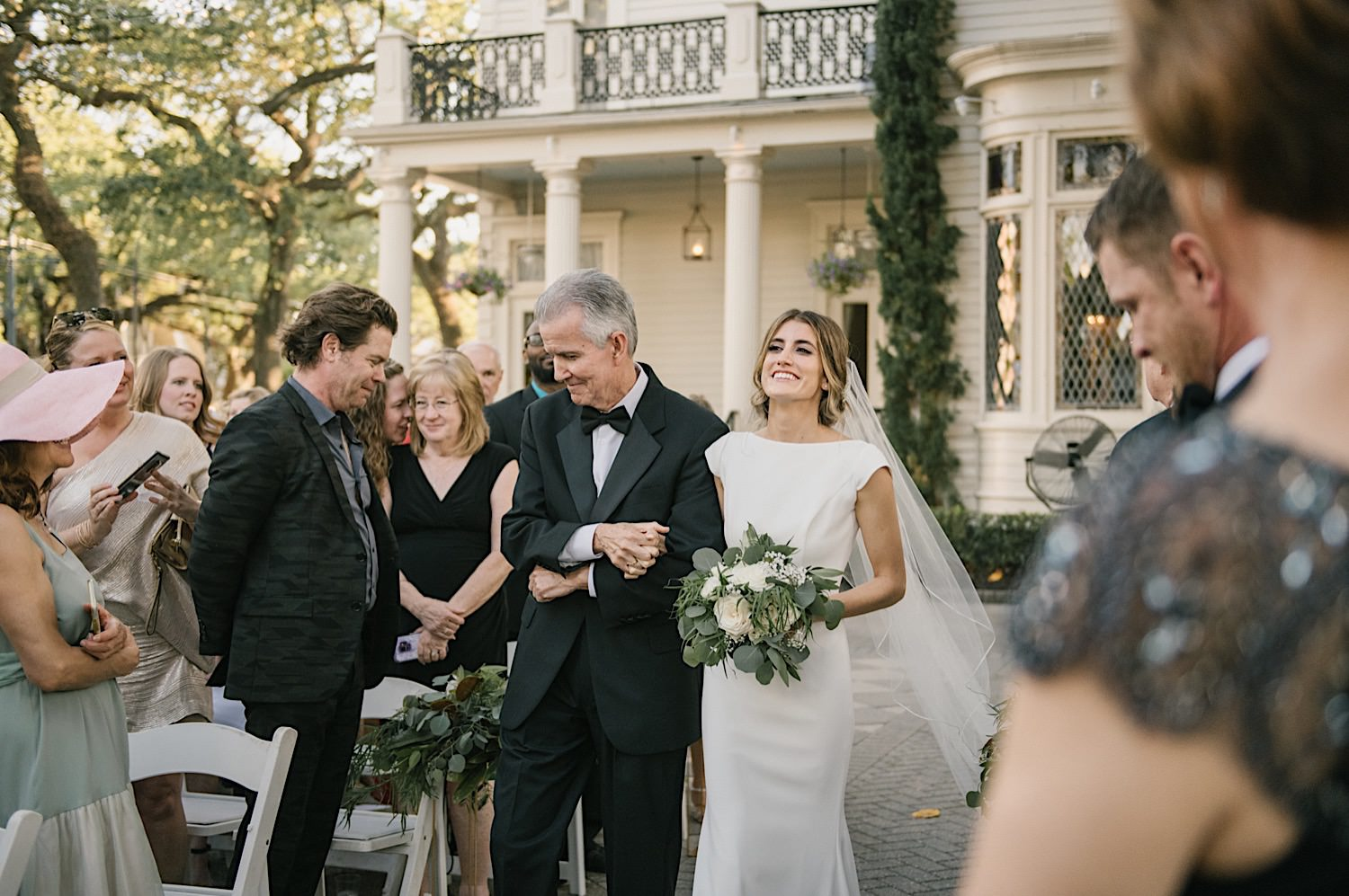 Taylors father walks her down the isle in the courtyard of the Elms Mansion.