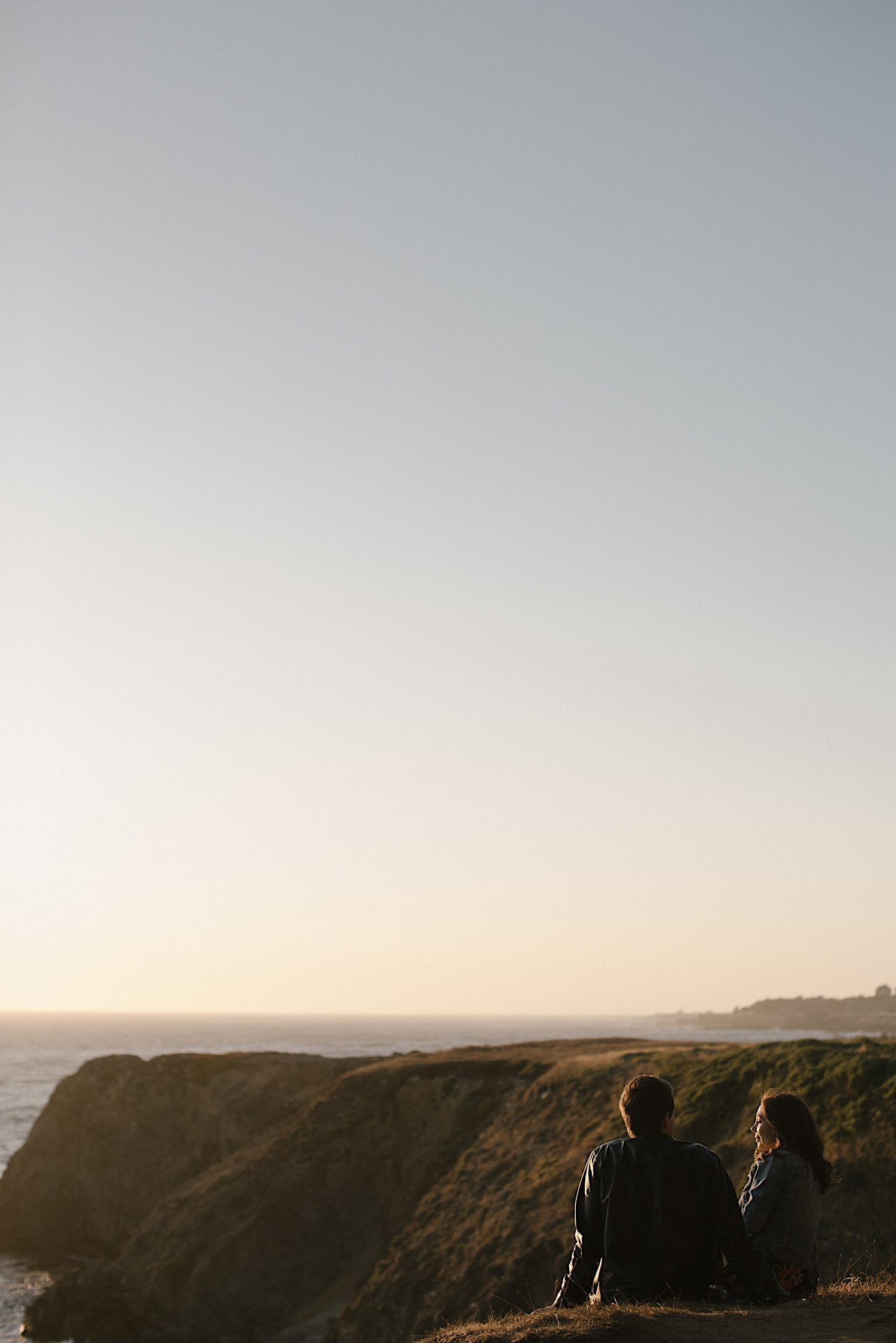 Adam and Vanessa sit along the cliff at Kelli Point for their Mendocino engagement session.
